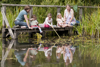 Two women and three young girls pond dipping from a wooden deck, The Wildlife Trusts