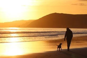 Sunset beach with man and his dog by Lauren Heather
