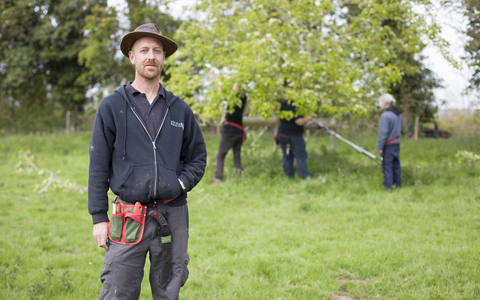 Laurence standing in an orchard
