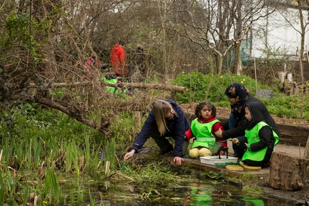 A nursery group peer into a pond on a visit to the centre for wildlife gardening in London